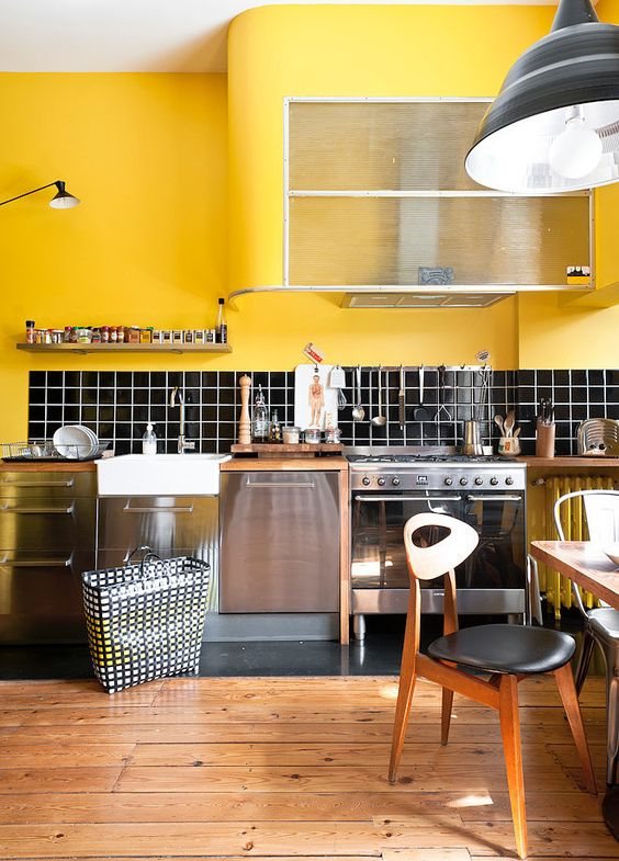 What an effect this kitchen has in bright yellow with black splash backs and stainless steel cabinet fronts