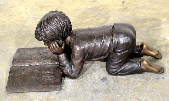 Place this bronze statue of a child reading a book in a place for quiet creativity in your garden.: