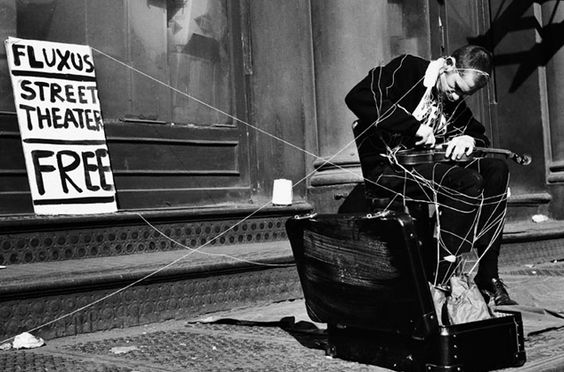 "Photograph of Ben Vautier wrapped in string from Takehisa Kosgui's Anima 1. He is playing a violin piece by George Maciunas. The photo was taken on May 23, 1964 at 359 Canal Street, New York City during the ""Street Events"" segment of the Flux Festival at Fluxhall."