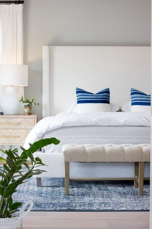 White Wingback Bed Displaying Blue Striped Pillows White Bedding
