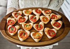 Blätterteig mit einer Kuchen Herzform ausstechen, Pizzakäse und Tomaten darauf legen und ab in den Ofen.