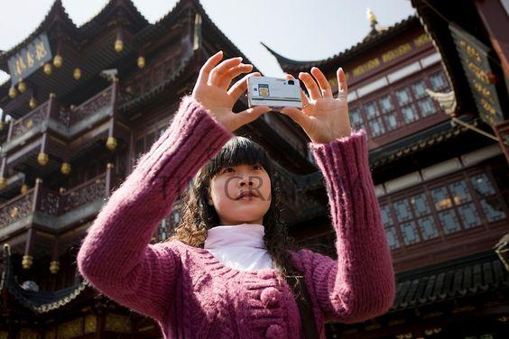 Young woman takes photograph on zigzag bridge at Yu Gardens Bazaar Market, Shanghai, China - Photo by Tim Graham