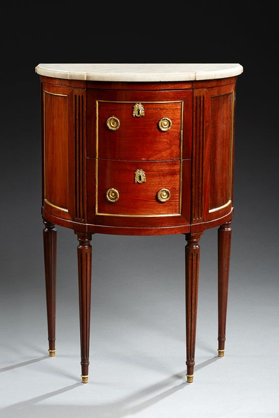 Small chest half moon mahogany veneer. It opens with two drawers without crosses. Amounts dishes triple wall. Fluted tapered legs. Termination of Louis XVI. plate of white marble veined gray.