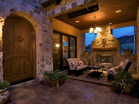 This Tuscan house's courtyard features a large old time door, with a sitting area and stone fireplace next to it.  The heater and fireplace makes this an efficient space for all seasons.
