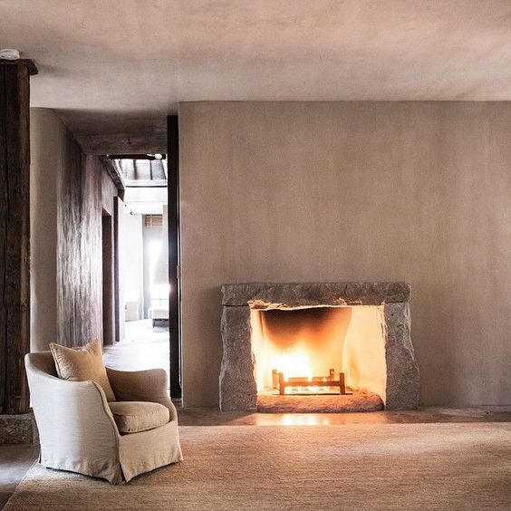 Ultimate cozy luxurious living room with #minimaldecor, rustic rugged stone fireplace, #plasterwalls and #Belgianlinen
