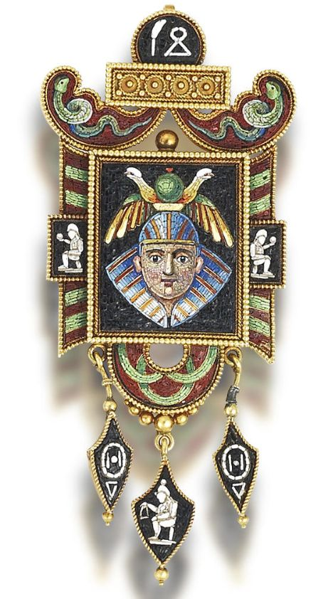 A gold and micromosaic brooch/pendant, circa 1865 Of ancient Egyptian inspiration, the elaborate cartouche depicting a pharaonic mask with two seated figures either side, in blue, red, yellow, green, white and black tesserae, within a patterned border of green and red micromosaic, surmounted by two writhing serpent motifs, a gold beadwork plaque, and black and white hieroglyph, suspending three black and white amphora pendants, glazed compartment to reverse, length 7.2cm
