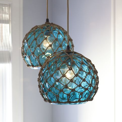 """Glass buoys were used by Japanese fishermen long ago to attach lines and hooks. This pendant is carefully crafted to resemble a found original, then it's surrounded with nautical rope to cast a patterned, ocean-blue light.  13"""" diameter, 13"""" high  At PBteen"""
