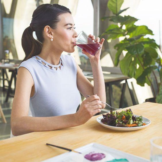 Una chica de perfil, morena peinada con coleta, sentada en un establecimiento público tomando una ensalada y bebiendo un complemento nutricional color vino