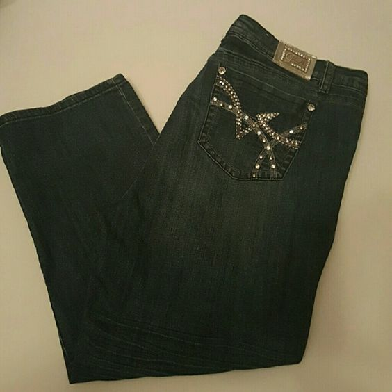 Denim blue jeans with rhinestone embeliahed pocket With brightly colored details, these flat back?Grace in LA Plus Size Jeans?Bootcut with Embroidered Faux Pockets are an ideal denim jean for the chic and fashionable woman! These jeans are a standout addition to your denim collection.  Featuring a medium wash with sanding and whiskering detail, these Grace in LA Plus Size Jeans feature embellished and embroidered designs on each pocket with metallic and grey stitch. gently used Grace In LA…