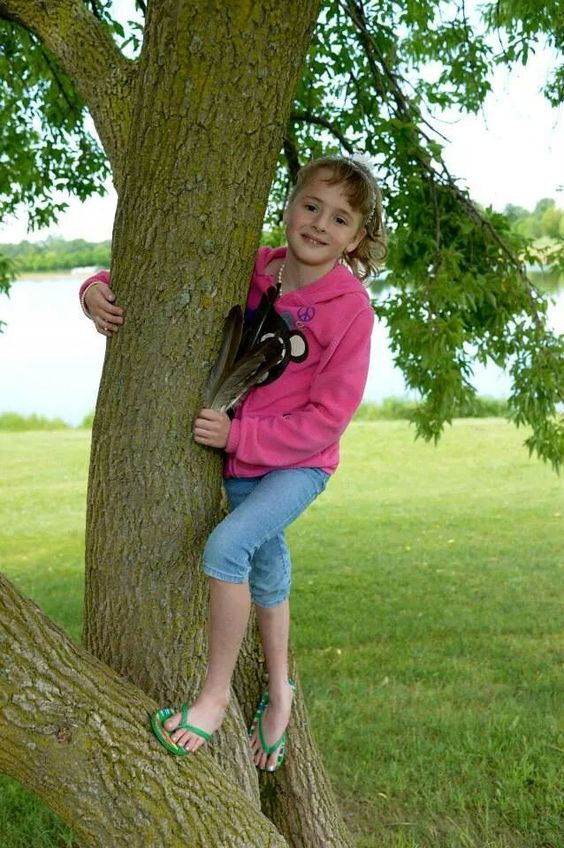 Kayanna standing in the tree with her feathers
