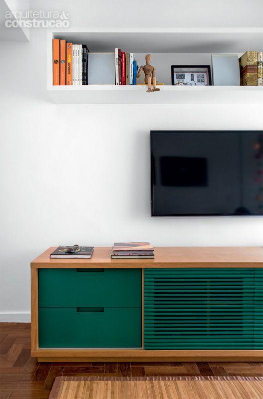 o aparador exibe acabamento de laca verde. mesmo fechada, a porta central, ripada, mantém ventilados os equipamentos de TV: