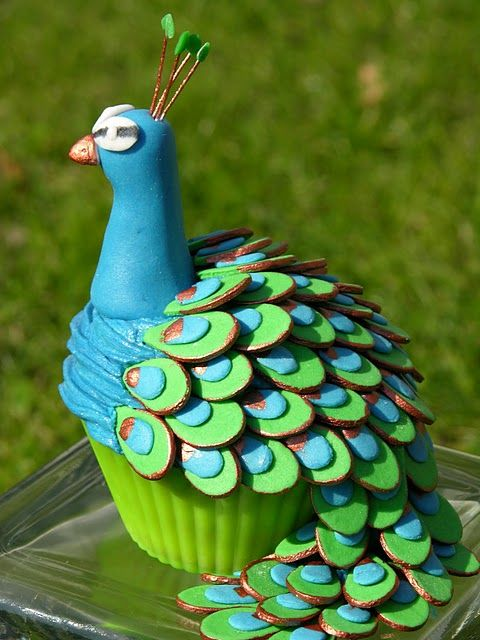 "A peacock  cupcake!...someone took a lot of time to individually cut out each ""feather"" and hand paint it!"