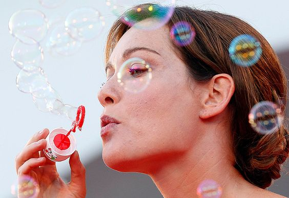 Italian actress Christiane Capotondi entertains journalists with soap bubbles