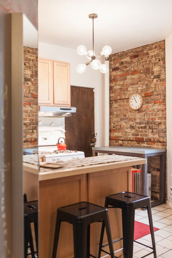 Apartment kitchen with unique light fixture and exposed brick walls