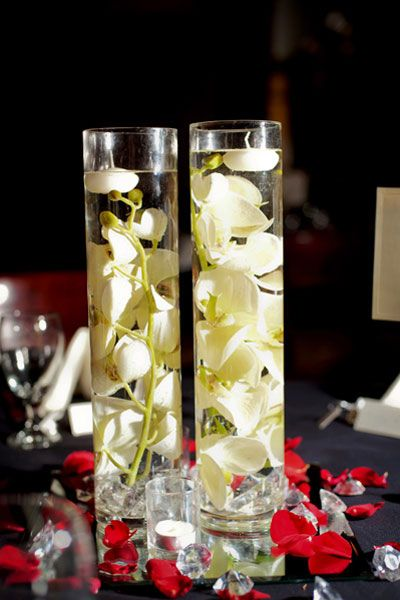 I like this idea for the reception tables. Maybe we can do some with red flowers some with white.