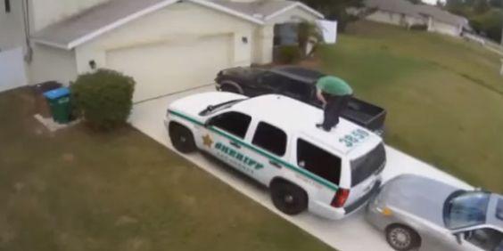 Imagens do circuito de vigilância de uma residência mostram o momento em que um homem, estaciona o seu carro por trás de um veículo policial, sai do carro sobe para cima do tejadilho do veículo …