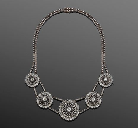 19TH CENTURY OLD MINE DIAMOND SPOKE NECKLACE Old mine diamond discs with spiraling rose cut diamond centers are suspended in a double row necklace with a total of approximately 26 carats of old mine diamonds set in silver top yellow gold. The necklace has its original attachments to fit the clusters as earrings and three brooches.