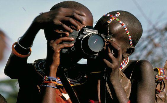 © Amos Nachoum. Masai Mara, Quênia, África.Crianças Masai brincam com a câmera do fotógrafo.