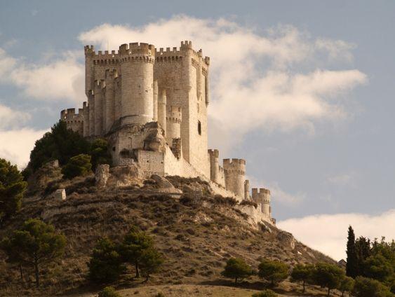 """CASTLES OF SPAIN - Castillo de Peñafiel, Valladolid. Existen referencias de su existencia desde el año 943, cuando era rey de León Ramiro II. En el 983 se apoderó del castillo, Almanzor (al-Mansur «el Victorioso»), hasta 1013, que fue conquistado por el conde Sancho García; a él se debe el cambio del nombre de Peña Falcón por el de Peñafiel, cuando el conde Sancho lo toma a los árabes y pronuncia la frase """"desde hoy en adelante esta será la peña más fiel de Castilla."""