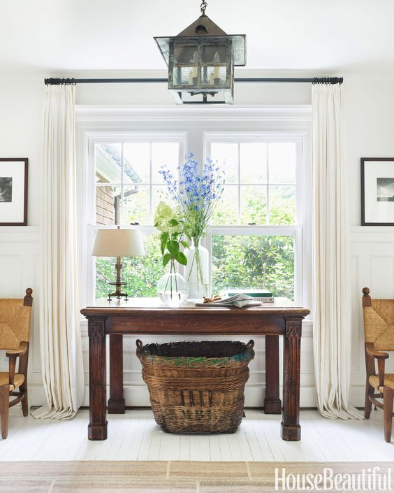 In the entry, an antique French basket provides storage for dog toys and leashes.   - HouseBeautiful.com