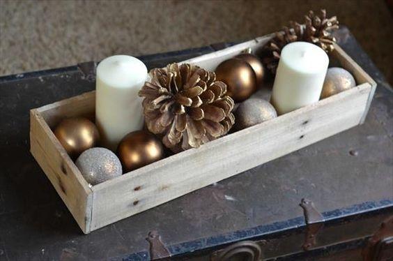 Un par de velas blancas, piñas y bolas en el mismo color; todo dentro de una caja de madera natural