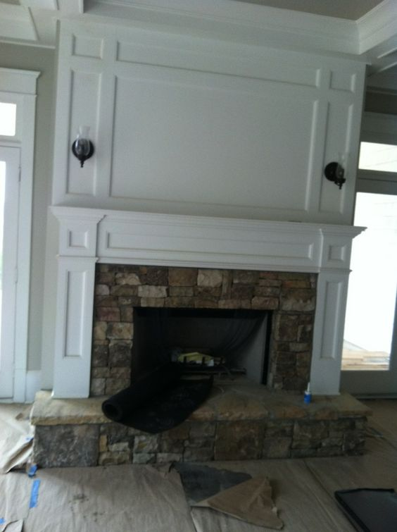 Fireplace with panels above to hide wiring for tv