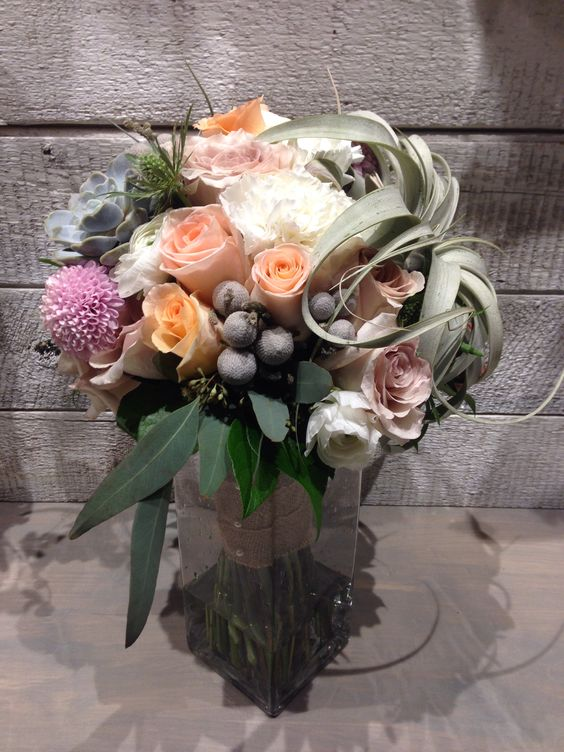 Bridal bouquet of roses, ranunculus, Russian button mums, talanzia, brunia berry, eucalyptus, and thistle. www.budsnbloom.com