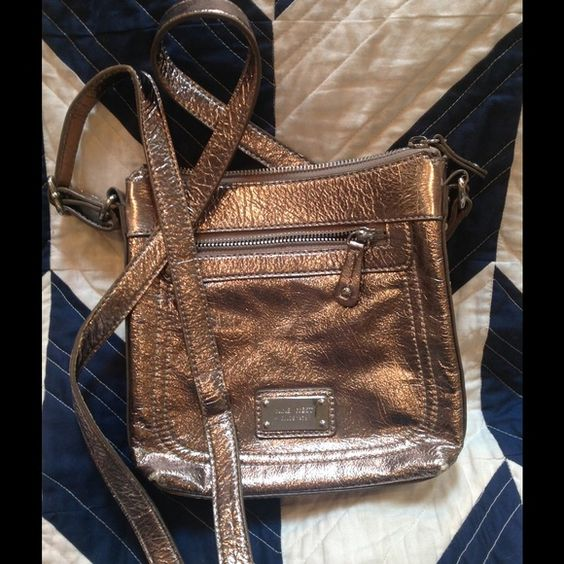Metallic silver Nine West cross body Bright metallic silver, good smaller size with convenient from zippered pocket. Ready for a new owner, good condition with some rubbing in the corners as shown in pics. Nine West Bags Crossbody Bags