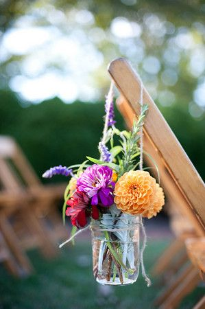 Rustic flowers in a mason jar, hanging on a chair with twine