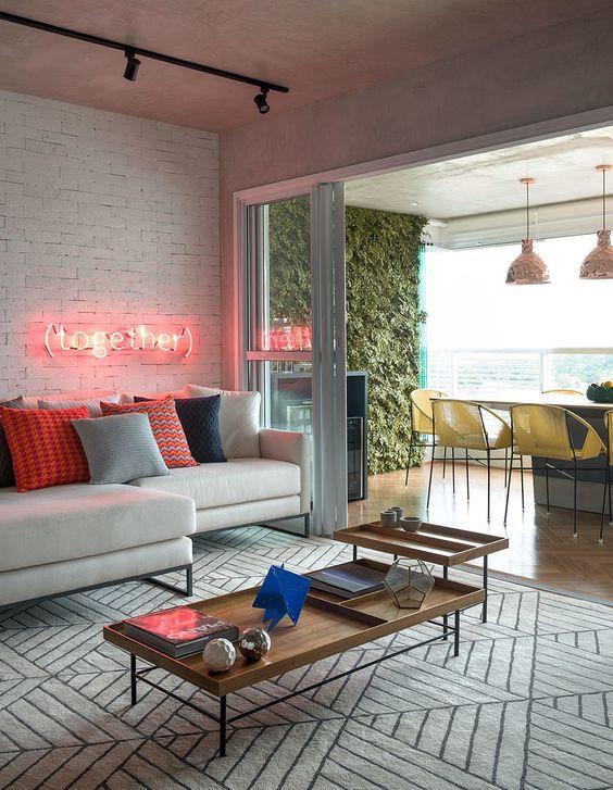 Decoração de apartamento criativo. Na sala, cimento queimado, parede de tijolinho aparente, sofá branco, neon, mesa de centro com adornos e luz natural.