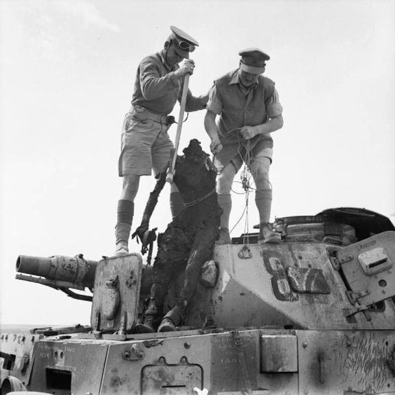 The sad reality of war. Two Commonwealth soldiers pull the decapitated body of a German panzer IV tank driver. I looks like they using a pickaxe & a flag & the chords from the vehicles intercom system to pull the body out.
