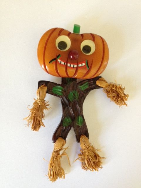 "RARE hand carved and painted Bakelite and wood Pumpkin head Scarecrow with googly eyes brooch pin. The pumpkin head is Bakelite, the body is wood, and real straw at his sleeves and feet. Measures 4-3/4"" tall! Sold for $8K on eBay Oct 2, 2013."