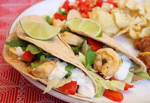 Tequila- Lime Shrimp Tacos w/ Chipotle Cream: garlic, sour cream, sauce, tequila, orange juice, shrimp, red bell pepper, flour tortillas, fresh cilantro, vegetable oil, ground cumin, salt, purple onion, chipotle chile, iceberg lettuce, shrimp, tequila, white sugar, sour cream, garlic, purple onion, chipotle chile, adobo sauce, ground cumin, salt, fresh cilantro, lime juice, vegetable oil, red bell pepper, purple onion, flour tortillas, iceberg lettuce, fresh cilantro
