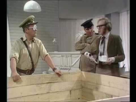 """The Goodies - South Africa Advert scene. Way ahead of their time in satirizing apartheid in South Africa. Grahame enters the South African tourist board with a sign that says, """"Through the door and turn white."""""""