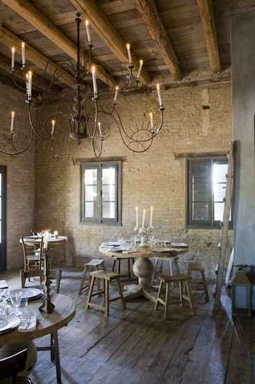 French country farmhouse dining room with huge chandelier, rustic decor, and stone walls. #frenchfarmhouse #frenchcountry #diningroom #provence #rusticdecor