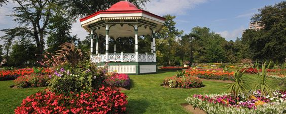 A gazebo sits in a park amid circular arrangements of flowers in bloom