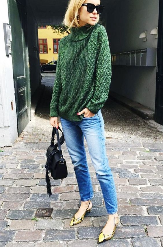 Pernille Teisbaek wears a green turtleneck sweater with blue jeans, a saddle bag, and slingback snake-print pumps: