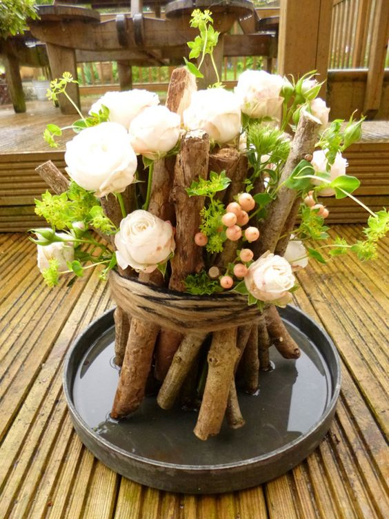 Check out this rather unique bouquet of flowers. White roses are partnered with peach colored berries and bunched together with thin and thick twigs in varying lengths. They are then bound together by a brown rope completing the rustic vice the arrangement gives off.: