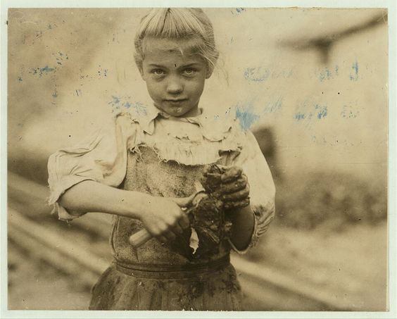 7-year old Rosie. Regular oyster shucker. Her second year at it. Illiterate. Works all day. Shucks only a few pots a day. (Showing process) Varn & Platt Canning Co. Location: Bluffton, South Carolina 1913 Photo by Lewis Hine