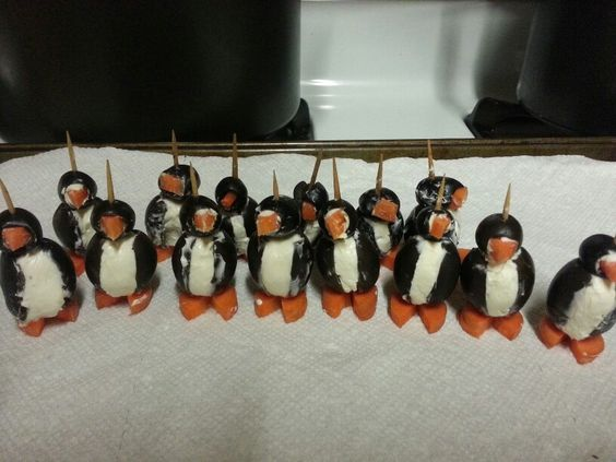Penguins made from slices of carrot,  a big and small black olive,  cream cheese and a tooth pick