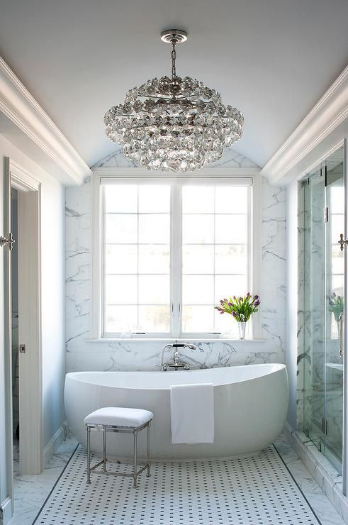 White and gray bathroom features a gray barrel ceiling accented with a tiered crystal chandelier illuminating an egg shaped tub and a vintage style hand held tub filler and a Restoration Hardware Newbury Bath Stool placed atop a black and white diamond pattern tiled floor.