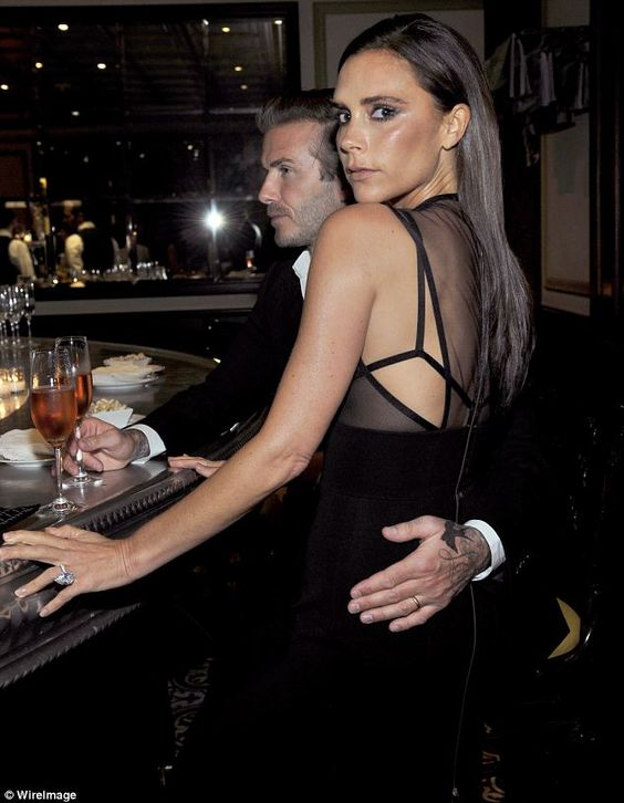Hands-on: David Beckham tenderly caresses his wife's back at the fashion dinner