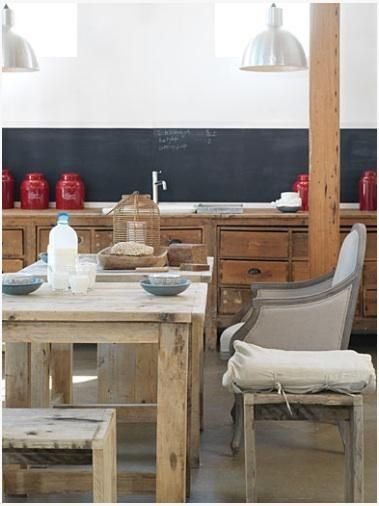 salvaged kitchen cabinets, simple teak tables and benches, industrial steel lights, unexpected profile of upholstered Bergere chair.  chalkboard-painted backsplash