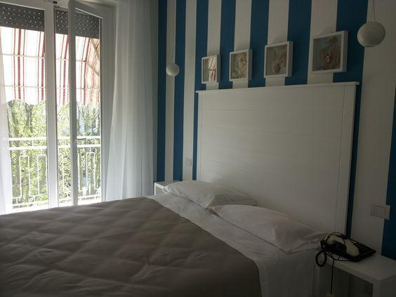 Camera hotel, testata letto in legno su misura.