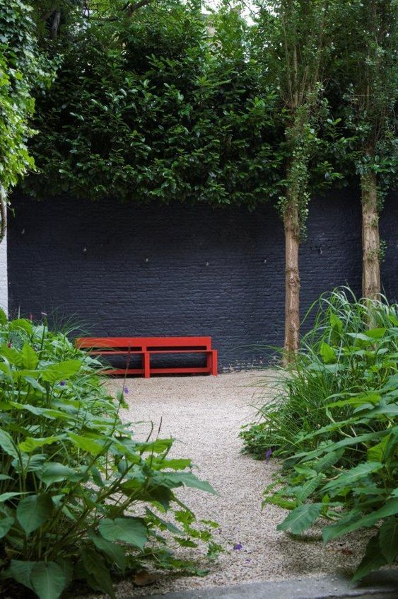 Le jardin passe au noir Gardens Grey walls and Red bench