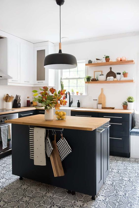 Learn how to paint kitchen cabinets like a pro with this easy tutorial by Aniko, from Place of My Taste. Aniko used BEHR Paint in Ultra Pure White and Night Club to create a two-tone color palette for her modern kitchen makeover. Then, she added open shelving, butcher block countertops, a patterned tile floor, and a bright white tile backsplash to tie her new style together.