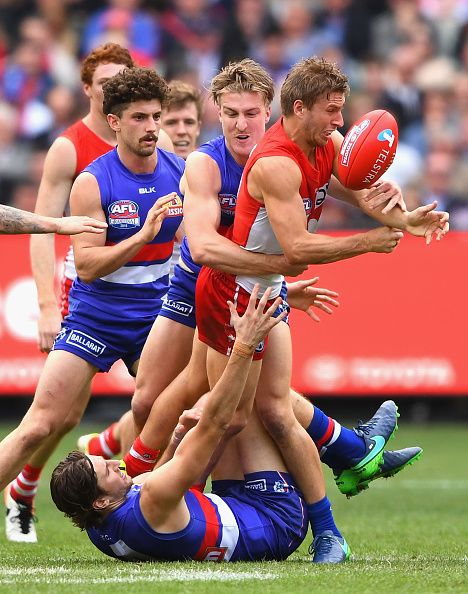 #AFLGF2016 Kieren Jack of the Swans handballs whilst being tackled by Shane Biggs of the Bulldogs during the 2016 AFL Grand Final match between the Sydney Swans...