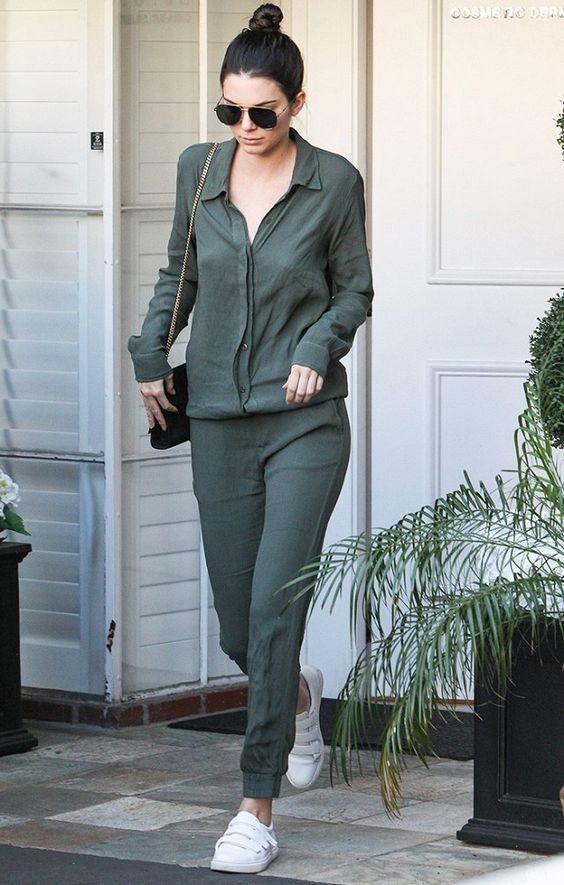 Kendall Jenner pairs white velcro strap sneakers with an olive green jumpsuit