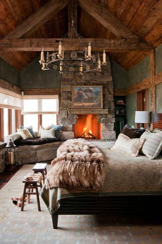 Chic, rustic and cozy winter ski chalet bedroom with dramatic candle chandelier pendant light, fur blanket, roaring stone edged fireplace, built in stone bench covered with cozy pillows, wood paneled walls, stools at the foot of the bed, and a soft carpet underfoot.