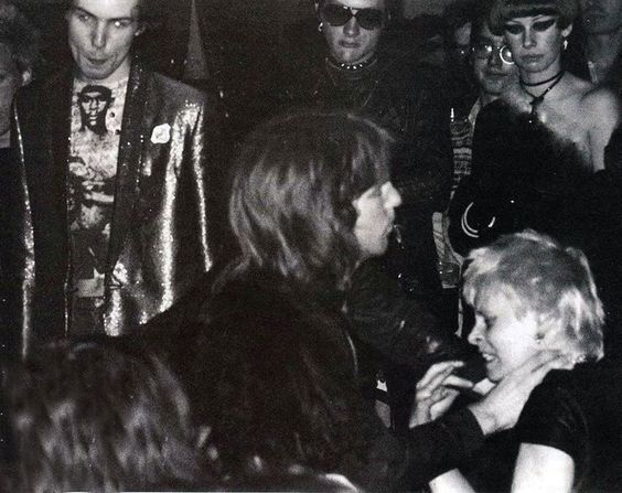 """Sid Vicious and Dave Vanian watching Vivienne Westwood getting beaten at a Sex Pistols show 1976. Paul Saint Savage: """"That guy's about to get a beat down in a few seconds from SEX shop workers and friends as well as the band. I read stories that she was antagonizing that dude for having long hair."""" Hervé Labyre: """" Westwood started a fight with members of the audience (rumours say it was because she was feeling """"bored"""") and that's how things went. McLaren then joined, and the band followed."""